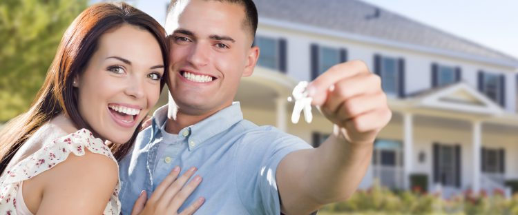 Mixed Race Excited Military Couple In Front of New Home Showing Off Their House Keys.